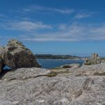 rocky granite outcrop with small beach in the far background