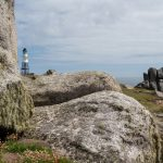 small automated lighthouse in the background set on a granite rocky hill