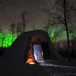 green aurora behind a sami hut covered in snow lit from within by a fire