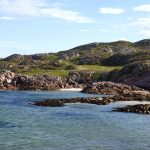 sea and small beach coves n the foreground with a grassy granite rocky outcrop in the background