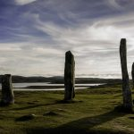 part of a standing stone circle getting near sunset with a loch in the background