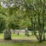 old standing stones with a stone cairn in the background