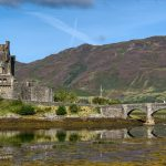 old castle with a bridge over a loch on a sunny day