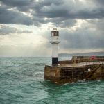 small lighthouse at end of a harbour in stormy sky with sun breaking through