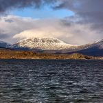 lake with a snow-sprinkled mountain in the background lit by the sun peaking through a hole in the clouds above